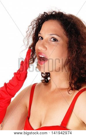 A young woman holding her hand for her open mouth telling a secret with red cloves isolated for white background.