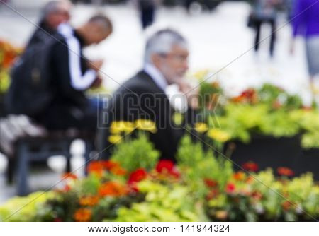 Attractive unrecognizable man sitting on the bench in the street. Blurred image unfocused.