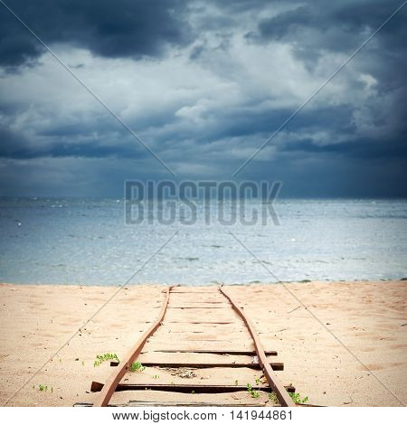 Old Rusted Railway Goes Over Sandy Beach