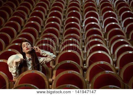 portrait of a pretty real girl hipster in a movie theater wearing hat, dreaming alone