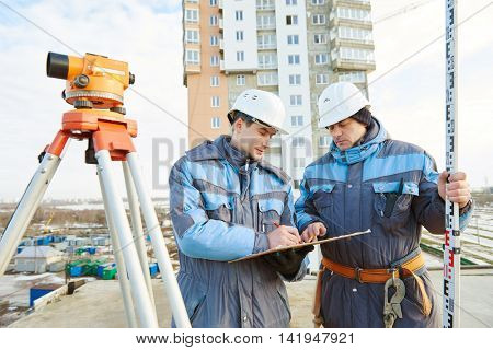 Surveyor workers with level at construction site