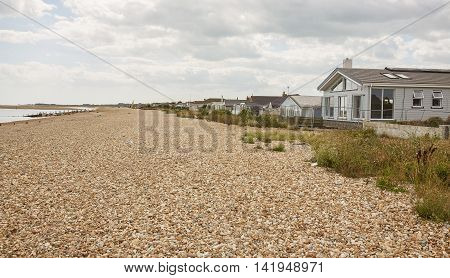 August 2016, Pagham West Sussex, UK. Pagham Beach and Seafront Homes.