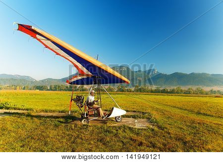 Motor hang glider close up on the ground and man