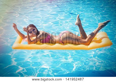 Portraito f a happy woman lying on air mattress in the swimming pool outdoors