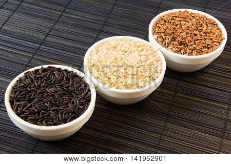black red and white unpolished rice in white plates on a black straw mat