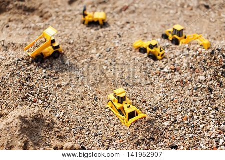 toy cars in sand quarry. yellow toy cars on construction site. selective focus