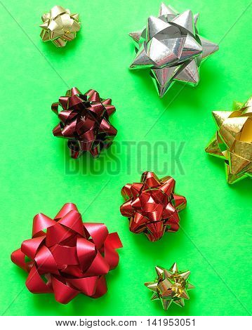A selection of colorful gift bows isolated on a green background