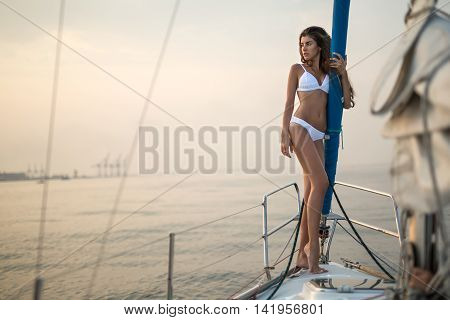 Cute girl stands on the yacht in a white swimsuit and holds the mast on the background of the sea and the sky. She looks to the right with parted lips. Outdoors. Horizontal.
