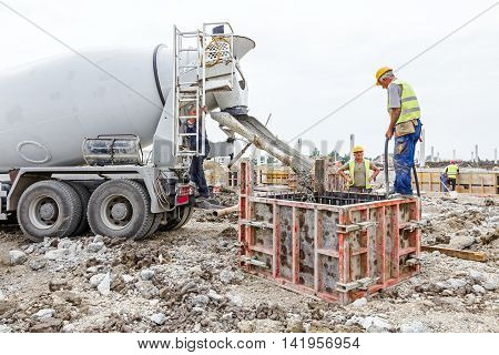 Zrenjanin Vojvodina Serbia - May 21 2015: Workers at building site are pouring concrete in mold from mixer truck.