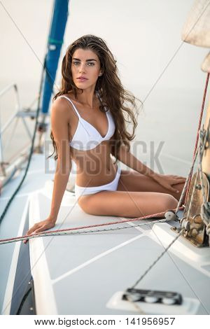 Sun-tanned girl in a white swimsuit sits on the yacht and looks into the camera with parted lips on the sea background. She leans on the right hand while left hand is on the left knee. Vertical.