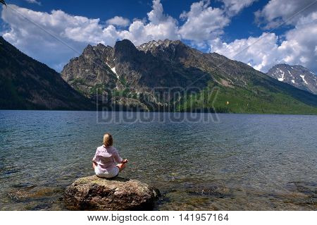 Woman sitting by lake and mountains. Jenny Lake in Grand Tetons National Park Jackson Wyoming.