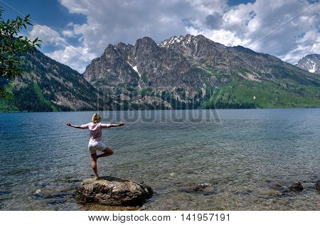 Woman in yoga pose meditating by lake and mountains. Jenny Lake in Grand Tetons National Park Jackson Wyoming.