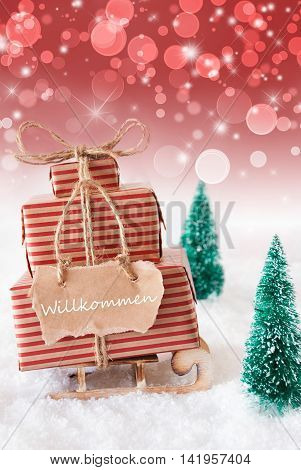 Vertical Image Of Sleigh Or Sled With Christmas Gifts Or Presents. Snowy Scenery With Snow And Trees. Red Sparkling Background With Bokeh. Label With German Text Willkommen Means Welcome