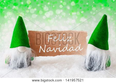 Christmas Greeting Card With Two Green Gnomes. Sparkling Bokeh And Natural Background With Snow. Spanish Text Feliz Navidad Means Merry Christmas