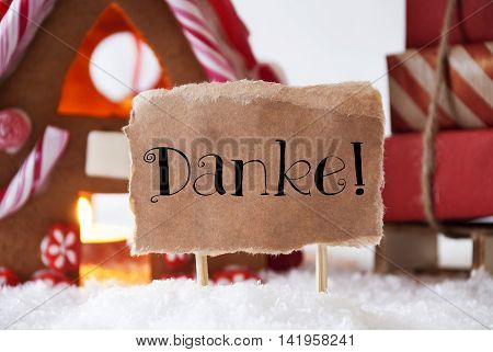 Gingerbread House In Snowy Scenery As Christmas Decoration. Sleigh With Christmas Gifts Or Presents. Label With German Text Danke Means Thank You