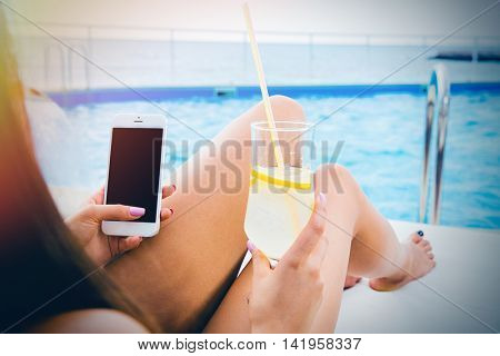 Portrait of a girl lying on deckchair with smartphone and cocktail outdoors