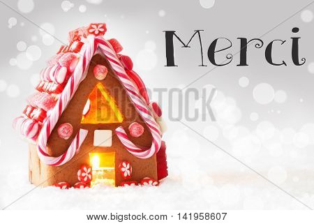 Gingerbread House In Snowy Scenery As Christmas Decoration. Candlelight For Romantic Atmosphere. Silver Background With Bokeh Effect. French Text Merci Means Thank You