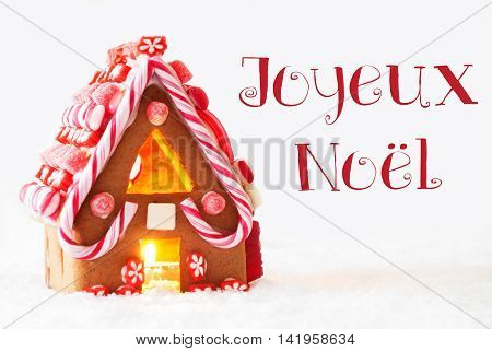 Gingerbread House In Snowy Scenery As Christmas Decoration With White Background. Candlelight For Romantic Atmosphere. French Text Joyeux Noel Means Merry Christmas