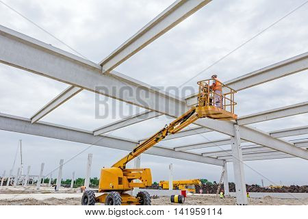 High elevated cherry picker with rigger on construction site.