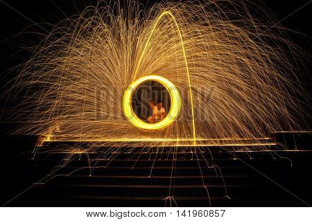 Hot Golden Sparks Flying from Man Spinning Burning Steel Wool on the Stair. Long Exposure Photography using Steel Wool Burning.