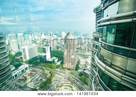 Luala Lumpur, Malaysia- October 11, 2013: Though window of Petronas Towers from observation deck urban view Kuala Lumpur with window framework reflections in sky area of imagereflections in sky area of image