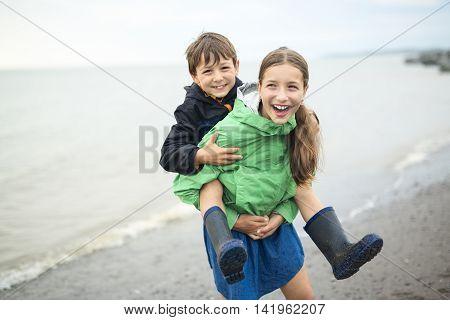 A boy and girl having fun on rain close to a sea