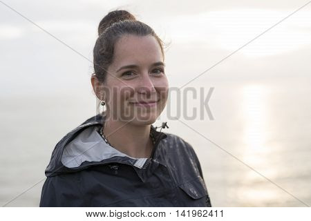 A Woman with raincoat on the side of the beach