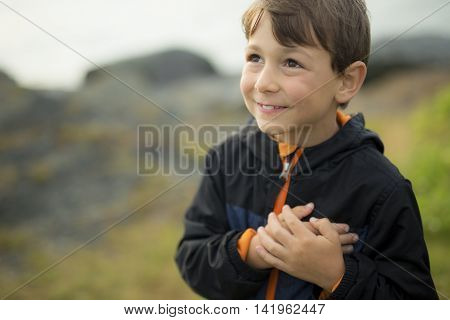 A boy close to the grass at sunset