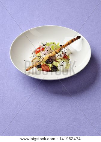Greek salad served with sesame breadstick on violet linen background