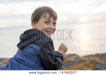A boy enjoying the sunset and having fun outside on a gray rainy