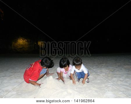 LAPU LAPU, CEBU / PHILIPPINES - JULY 28, 2011: Children play in the sand during the night at the beach of Shangri-La's Mactan Resort and Spa.