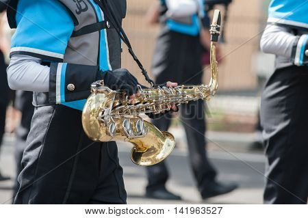 Teen saxophone player marching in the band.