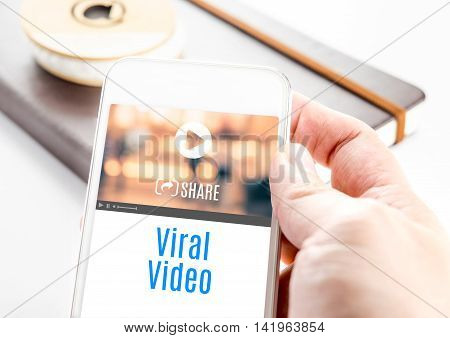 Close Up Hand Holding Smart Phone With Viral Video Word And Icons With Notebook At Background, Mobil