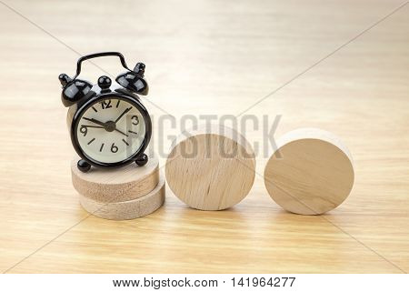 Black Alarm Clock On Stack Of Round Wood Piece With Blank Wood Piece On Light Wooden Table,business