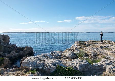 ROCKINGHAM,WA,AUSTRALIA-JULY 12,2016: Tourist taking in the peaceful Indian Ocean seascape from the limestone rock formations at Point Peron in Rockingham, Western Australia