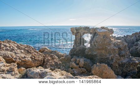 Natural limestone window and rugged coastal rock formation with the Indian Ocean seascape under a blue sky at Point Peron in Rockingham, Western Australia