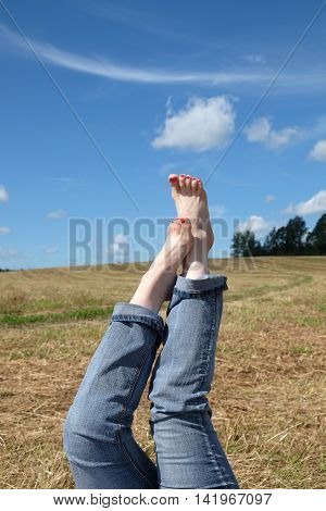 Side view  of beautiful playful female bare feet with red nails in rolled blue jeans close-up against summer nature landscape with meadow, sky and country road