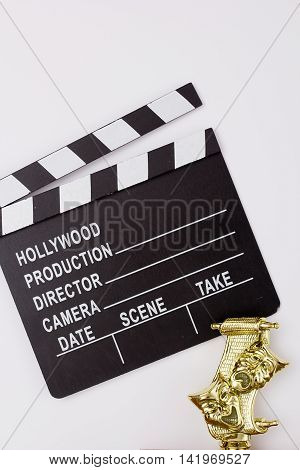 Theatrical mask and film clapper on a white background