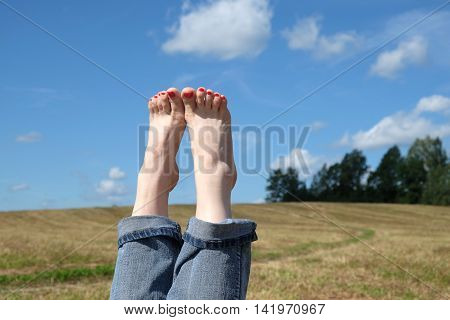 Beautiful playful female bare feet with red nails in rolled blue jeans close-up against summer nature landscape with meadow, sky closeup