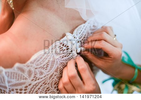 Garter on the leg of a bride, slim sexy bride in wedding luxury dress showing her silk garter with golden ribbon. woman have a final preparation for wedding ceremony. Wedding day moments