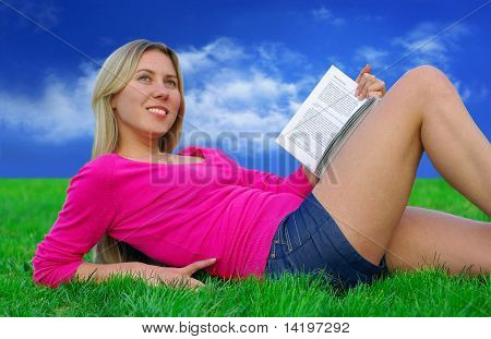Beautiful girl with book on the blue sky and green grass background