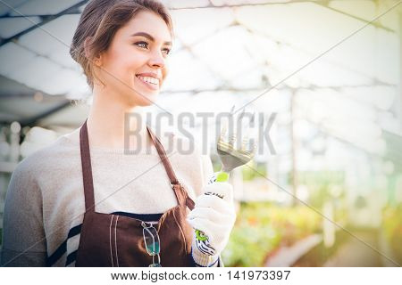 Cheerful pretty young woman gardener in apron holding fork for transplantation plants in greenhouse