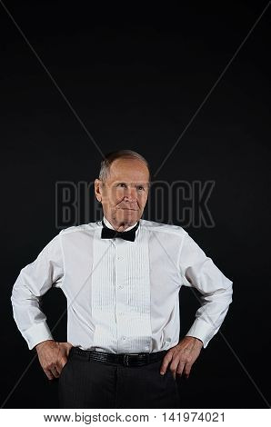 Man portrait in a white shirt and black bow with copy space, isolated on black background