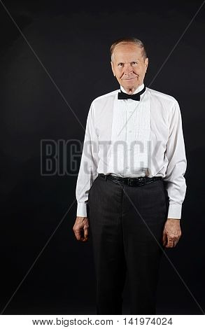 Smiling, happy man in a white shirt and black bow, senior man portrait with copy space, isolated on black background