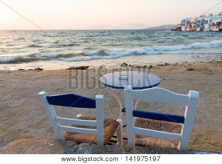 Empty blue chair and table at the beach of little venice area at Mykonos island in Greece