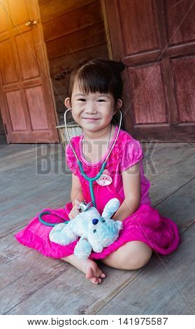 Adorable asian child playing doctor or nurse with plush toy bear with bright sunlight at home. Happy girl listens a stethoscope to toy. Playful girl role playing.