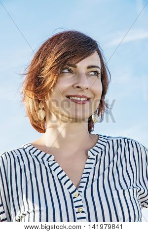Portrait of young caucasian woman in sunny outdoor. Beauty and fashion. Vertical composition. Positive emotions.