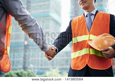 Cropped image of investor and contractor shaking hands
