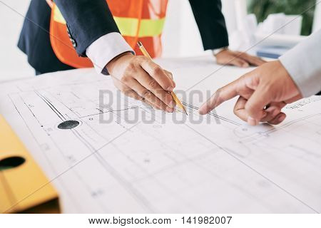 Engineer explaining blueprint to the investor of project