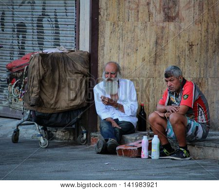BARCELONA/SPAIN - 18 JULY 2016: Homeless people next to a cart with their clothing on a central street in Barcelona